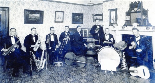 "Photo:Len Coyne's ""Selectra"" Band c.1930 pictured in what became the Coyne family's living room on the first floor of the Moot Hall.  Photographed in a room above the shop, the picture shows Len Coyne (second from left) and Frank Coyne on drums.  Arthur Coyne is 4th from left.  Note the loud-hailer (next to the bass drum) which was used by the vocalist in these days before microphones."
