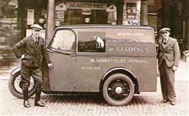 Photo:Above: Coynes' first motorised (3-wheeled) delivery vehicle.  Pictured outside the shop in the early 1930s are my uncle Jack Maidlow (left) and Len Coyne on the right.  The van was painted in Sherwood Foresters colours - green with red panels and gold lettering.  The picture left also shows Len Coyne in the early 1930s beside a selection of 'brand new and boxed' His Master's Voice table-top valve wireless sets.  One top of the pile is a box containing a separate 'all purpose' loudspeaker.