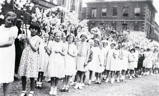 Photo:9.  After the judging was over the devices paraded around the town preceded by children with garlands of flowers.  Pictured here among the procession in 1938 or 1939 is Jean Ragsdale (third from left).
